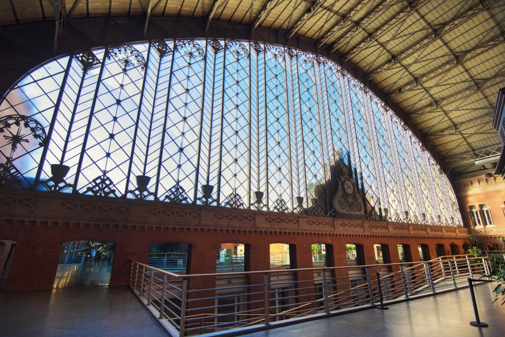 Looking our the large glass and wrought iron window at the front of Atocha train station in Madrid.