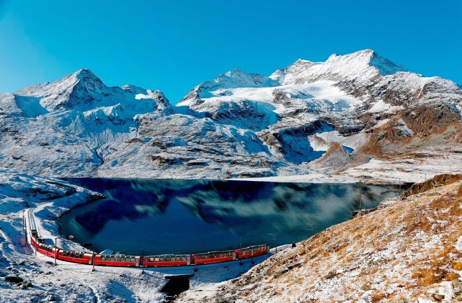 bernina express passing by snowy mountain